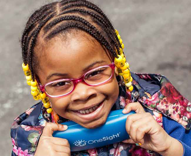 Smiling child wearing glasses and holding OneSight glasses case
