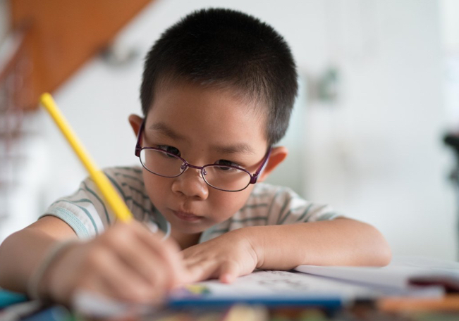 Young child writing with a pencil
